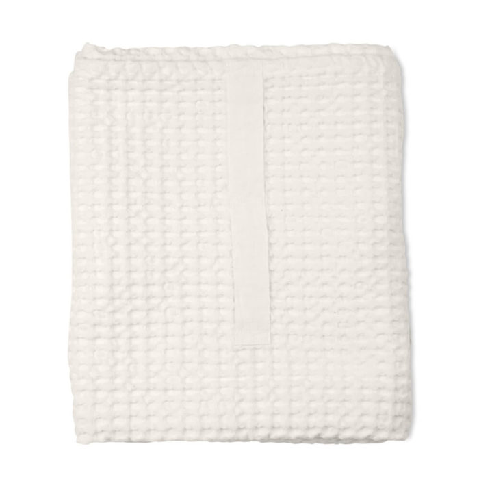 Imagine a big waffle towel and large throw blanket that's large enough to be like an adult snuggle blanket. Remember the mini version you perhaps had as a child? Well, here you have it in organic cotton with a luxurious and tactile waffle weave. The extra large throw and towel is multi-use as an absorbent large bath towel, a cosy sofa throw or large bedspread. And why not bring it along as as a pool towel or picnic blanket? You can choose the Scandinavian colour that best suits your style. Seen here in natural white. Size: 100 x 150 cm Material: 100% GOTS certified organic cotton Weaving: Waffle, grosgrain strap