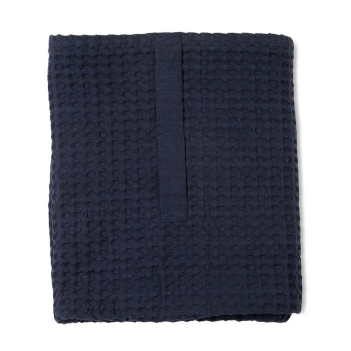 Imagine a big waffle towel and large throw blanket that's large enough to be like an adult snuggle blanket. Remember the mini version you perhaps had as a child? Well, here you have it in organic cotton with a luxurious and tactile waffle weave. The extra large throw and towel is multi-use as an absorbent large bath towel, a cosy sofa throw or large bedspread. And why not bring it along as as a pool towel or picnic blanket? You can choose the Scandinavian colour that best suits your style. Seen here in dark blue. Size: 100 x 150 cm Material: 100% GOTS certified organic cotton Weaving: Waffle, grosgrain strap