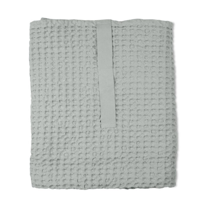 Imagine a big waffle towel and large throw blanket that's large enough to be like an adult snuggle blanket. Remember the mini version you perhaps had as a child? Well, here you have it in organic cotton with a luxurious and tactile waffle weave. The extra large throw and towel is multi-use as an absorbent large bath towel, a cosy sofa throw or large bedspread. And why not bring it along as as a pool towel or picnic blanket? You can choose the Scandinavian colour that best suits your style. Seen here in sky blue. Size: 100 x 150 cm Material: 100% GOTS certified organic cotton Weaving: Waffle, grosgrain strap