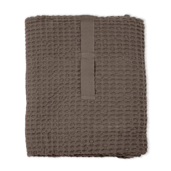 Imagine a big waffle towel and large throw blanket that's large enough to be like an adult snuggle blanket. Remember the mini version you perhaps had as a child? Well, here you have it in organic cotton with a luxurious and tactile waffle weave. The extra large throw and towel is multi-use as an absorbent large bath towel, a cosy sofa throw or large bedspread. And why not bring it along as as a pool towel or picnic blanket? You can choose the Scandinavian colour that best suits your style. Seen here in clay. Size: 100 x 150 cm Material: 100% GOTS certified organic cotton Weaving: Waffle, grosgrain strap