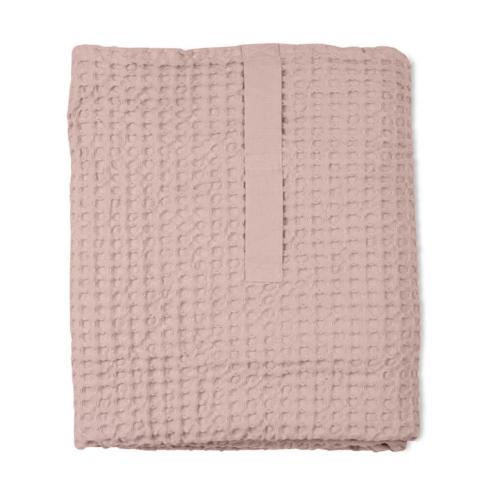 Imagine a big waffle towel and large throw blanket that's large enough to be like an adult snuggle blanket. Remember the mini version you perhaps had as a child? Well, here you have it in organic cotton with a luxurious and tactile waffle weave. The extra large throw and towel is multi-use as an absorbent large bath towel, a cosy sofa throw or large bedspread. And why not bring it along as as a pool towel or picnic blanket? You can choose the Scandinavian colour that best suits your style. Seen here in rose. Size: 100 x 150 cm Material: 100% GOTS certified organic cotton Weaving: Waffle, grosgrain strap
