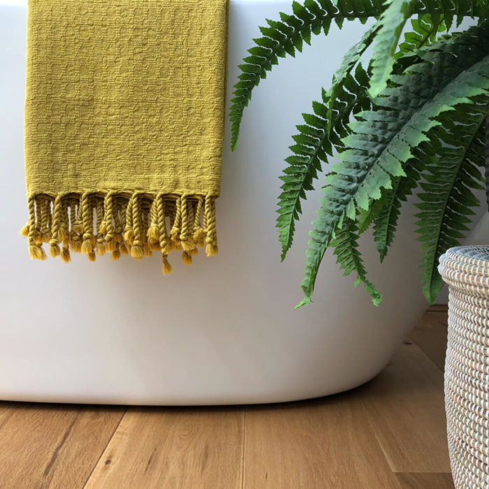 Ela Turkish bath towel in gorse yellow. Jacquard woven from heavy weighted absorbent cotton that's quick to dry. With simple, textured design. Finished with hand twisted and knotted fringe. It takes up 1/3 of the space of a standard towel. 90 x 180cm