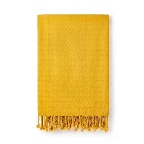 Ela Turkish bath towel in gorse yellow. Jacquard woven from heavy weighted yet quick drying cotton with simple, textured design. Finished with hand twisted and knotted fringe. It takes up 1/3 of the space of a standard towel. 90 x 180cm