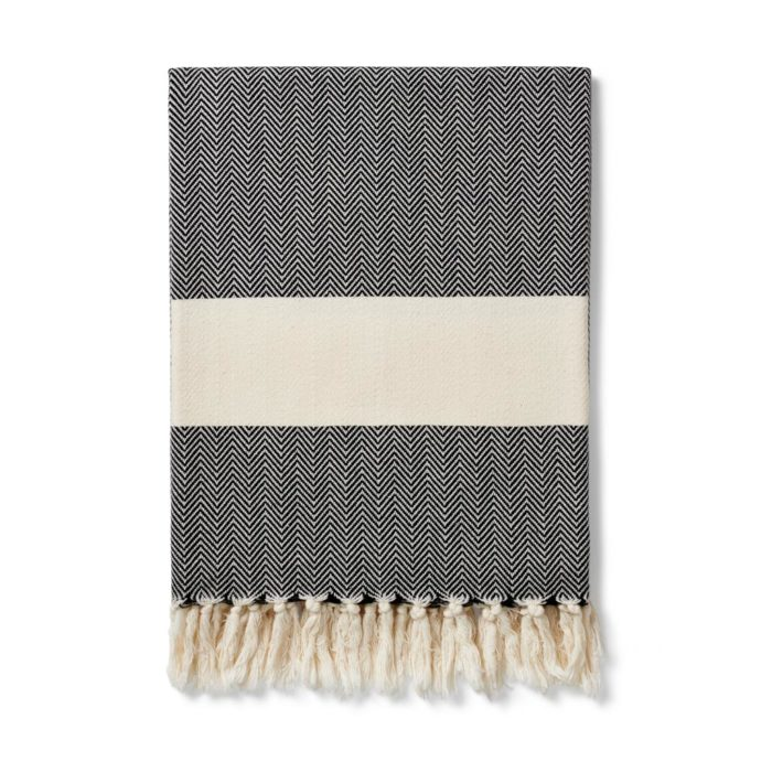 The Ferah organic cotton towel is a classic herringbone weave peshtemal with ecru block stripe & hand knotted tassels. Use it as a lightweight and quick drying towel, scarf, throw or sarong! 100 x 180 cm Seen here in ink black