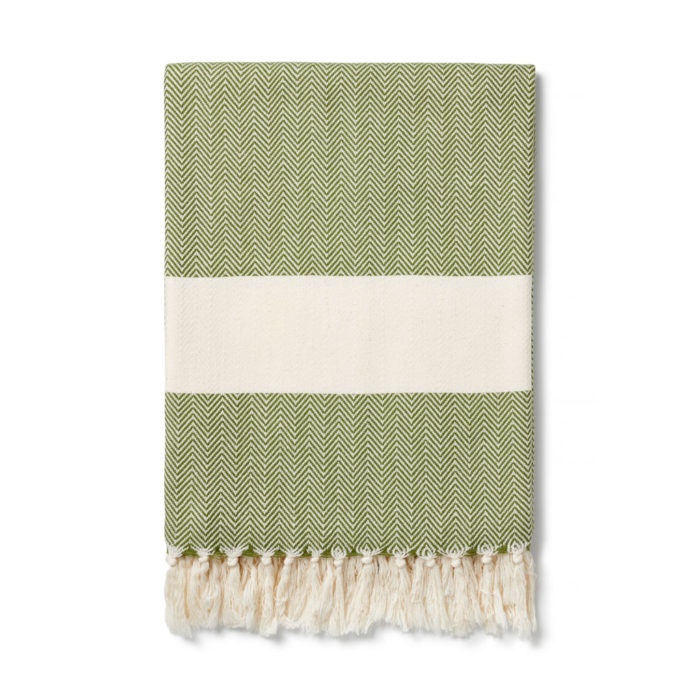 The Ferah organic cotton towel is a classic herringbone weave peshtemal with ecru block stripe & hand knotted tassels. Use it as a lightweight and quick drying towel, scarf, throw or sarong! 100 x 180 cm Seen here in moss green.