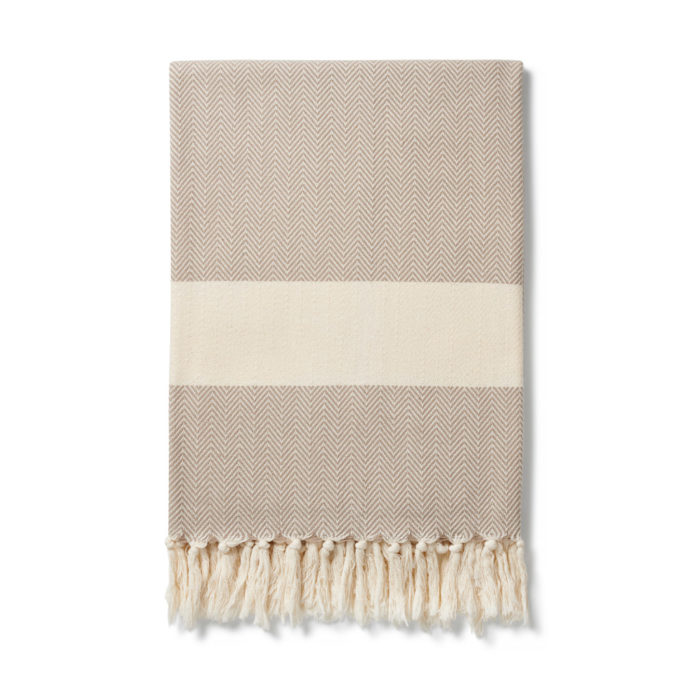 The Ferah organic cotton towel is a classic herringbone weave peshtemal with ecru block stripe & hand knotted tassels. Use it as a lightweight and quick drying towel, scarf, throw or sarong! 100 x 180 cm Seen here in oyster grey.