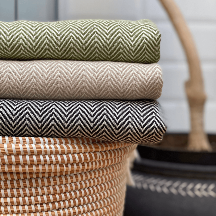 The Ferah organic cotton towel is a classic herringbone weave peshtemal with ecru block stripe & hand knotted tassels. Use it as a lightweight and quick drying towel, scarf, throw or sarong! 100 x 180 cm Seen here ink, oyster and moss.