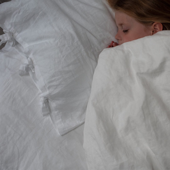 Toddler or child white linen pillowcase (2 sizes available) - organic linen & bamboo Made from a soft blend of organic linen and bamboo. This affordable child or toddler pillowcase in pure white is soft, sustainable, hypoallergenic and moisture absorbent. The flax linen and bamboo combination makes Flax Shop bedding even softer and easier to look after, without losing any of the great qualities linen of pure linen. The fibres in this organic bedding are naturally antibacterial, hypoallergenic and moisture absorbent. These sustainable bed linens are also kind to the skin, due to the fabric's neutral pH level and its ability to help regulate the body temperature of its users. Both linen and bamboo are advisable for even the most sensitive and eczema prone skin, becoming the perfect solution to ensure a good night's sleep. Both the child and toddler pillowcase is enclosed by linen ties. Seen here is also the duvet cover and fitted sheet. Sizes: Toddler pillowcase: 36cm x 58cm Children's pillowcase: 50cm x 75cm Features: Soft Crease resistant Twice as durable as cotton Sustainable Hypoallergenic Antibacterial Moisture absorbent Becomes softer with each wash. Material: 85% linen / 15% bamboo