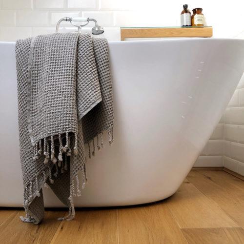 Rulo waffle weave towel in Lichen draped over the bath.