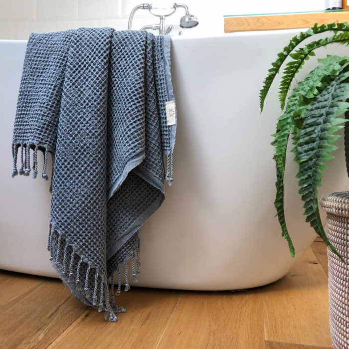 Rulo peshtemal draped over the bath. Traditionally woven in Turkey using eco conscious cotton. This colour is Marine blue.