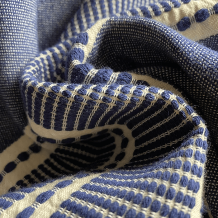 Sefa is a super soft deluxe and versatile peshtemal that has been traditionally loomed by master weavers from GOTS certified organic cotton. Size: 90 x 170 cm. Seen here in close up in Navy.