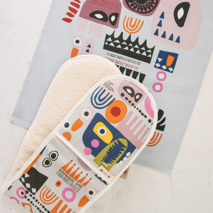 "The ""Shapes"" colourful oven gloves and matching tea towel in an abstract, bold and contemporary design. This is the Shapes 2, in a blue tone, featuring bright and colourful combinations of abstract patterns resembling faces. (Design 1 has more yellow). You can mix and match the Shapes colourful oven gloves with tea towels in the same design. You can see the whole Softer + Wild collection here. 85 x 20 cm 100% European cotton with towelling back Heat resistant Hanging loop Wash at 40 degrees Made in Great Britain Softer + Wild dyes are gentle and water based, giving a rustic, organic feel to their products – perfect for presents and giving you comfort, luxe and design to the table and your interior. The fabrics are robust, with a beautiful design that you can keep for many years. The more you use it, the more it softens and relaxes, decorating your home in vibrant colours."