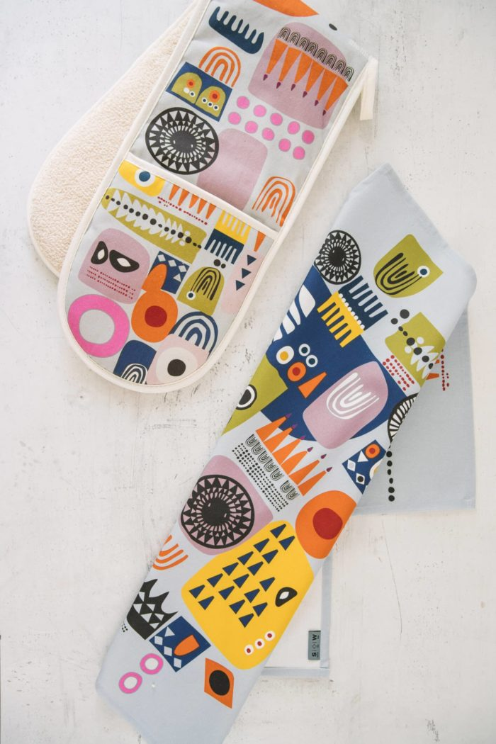 "The ""Shapes"" colourful oven gloves and matching tea towel in an abstract, bold and contemporary design. This is the Shapes 1, in a yellow tone, featuring bright and colourful combinations of abstract patterns resembling faces. (Design 2 has a blue dominance). You can mix and match the Shapes colourful oven gloves with tea towels in the same design. You can see the whole Softer + Wild collection here. 85 x 20 cm 100% European cotton with towelling back Heat resistant Hanging loop Wash at 40 degrees Made in Great Britain Softer + Wild dyes are gentle and water based, giving a rustic, organic feel to their products – perfect for presents and giving you comfort, luxe and design to the table and your interior. The fabrics are robust, with a beautiful design that you can keep for many years. The more you use it, the more it softens and relaxes, decorating your home in vibrant colours."