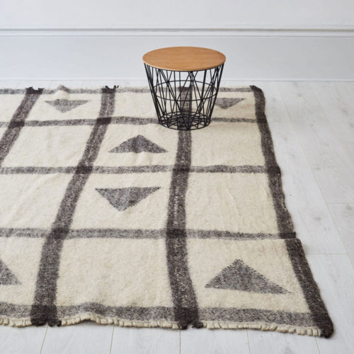 "Nuptse Radhi Himalayan sheeps wool rug. Hand woven in Nepal on traditional back-strap looms. Using un-dyed local sheep's wool, these boiled sheeps wool rugs are then washed in hot water to felt the wool. The result is a thick, hard wearing and washable monochrome rug in grey and white, perfect for a neutral, natural home. Anti-slip underlay also available in pre-cut sizes. Simply trim to fit on installation. Large 175 x 225cm [88"" x 69""] Washable Pure Himalayan Wool Handwoven, felted These sheeps wool rugs are made by Radhi Weavers. Based on traditional radhi produced for the local market in Nepal, these best selling rugs are often used as blankets, floor coverings and even worn to keep out the cold and rain. They're woven in the Himalayas by artisans using wool from local sheep, which is hand-spun. Stitch & Stitch use only the un-dyed wool in their fair trade rug designs - creamy white and a dark grey wool from black sheep. The radhi are first woven on simple back-strap looms, which can be set up anywhere - against a tree or a building. The looms are narrow, and the cloth woven on them is only about 36cm wide. To create a larger piece such as a carpet, several strips of cloth are sewn together by hand."