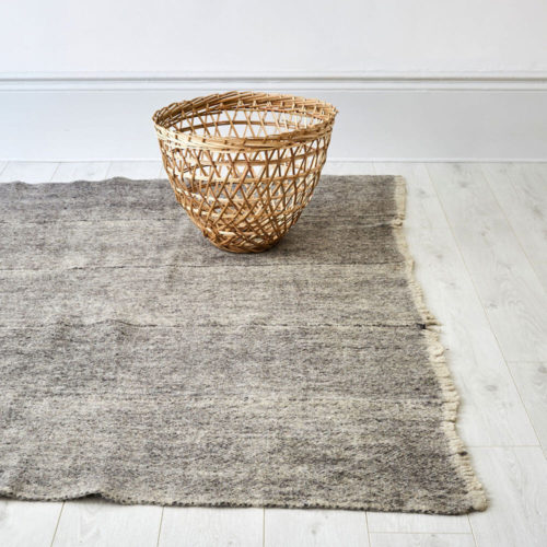"Himalayan grey wool rug. Hand woven in Nepal on traditional back-strap looms. Using un-dyed local sheep's wool, these boiled sheeps wool rugs are then washed in hot water to felt the wool. The result is a thick, hard wearing and washable monochrome grey wool rug, perfect for a neutral, natural home. Anti-slip underlay also available in pre-cut sizes. Simply trim to fit on installation. Small 166 x 144cm [65'"" x 57""] Large 175 x 225cm [88"" x 69""]. Washable, Pure Himalayan Wool. Handwoven, felted. These sheeps wool rugs are made by Radhi Weavers. Based on traditional radhi produced for the local market in Nepal, these best selling rugs are often used as blankets, floor coverings and even worn to keep out the cold and rain. They're woven in the Himalayas by artisans using wool from local sheep, which is hand-spun. Stitch & Stitch use only the un-dyed wool in their fair trade rug designs - creamy white and a dark grey wool from black sheep. The radhi are first woven on simple back-strap looms, which can be set up anywhere - against a tree or a building. The looms are narrow, and the cloth woven on them is only about 36cm wide. To create a larger piece such as a carpet, several strips of cloth are sewn together by hand."