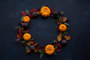 Halloween pumpkin wreath with orange pumpkins, dark green leaves and red ivy berries. These pumpkins are un-carved and unpainted, so can be cooked and eaten afterwards. Photo by Joanna Kosinska on Unsplash.