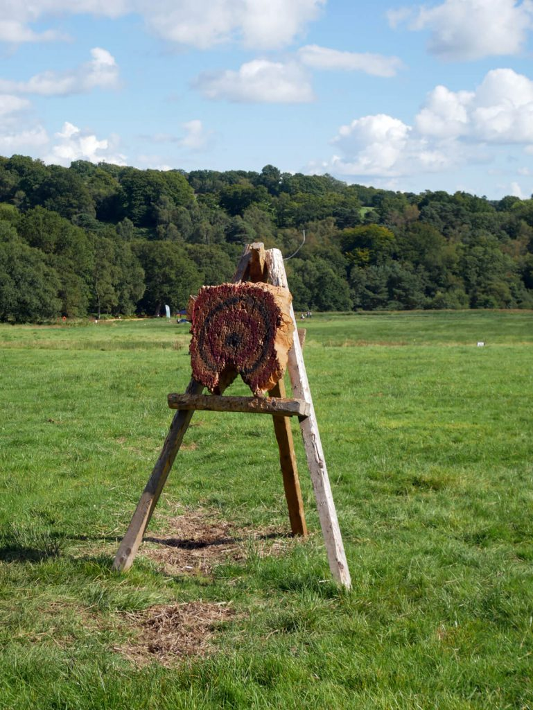 Axe throwing and cross bow practise at Into The Trees family festival at Pippingford Park in Ashdown Forest, Sussex.