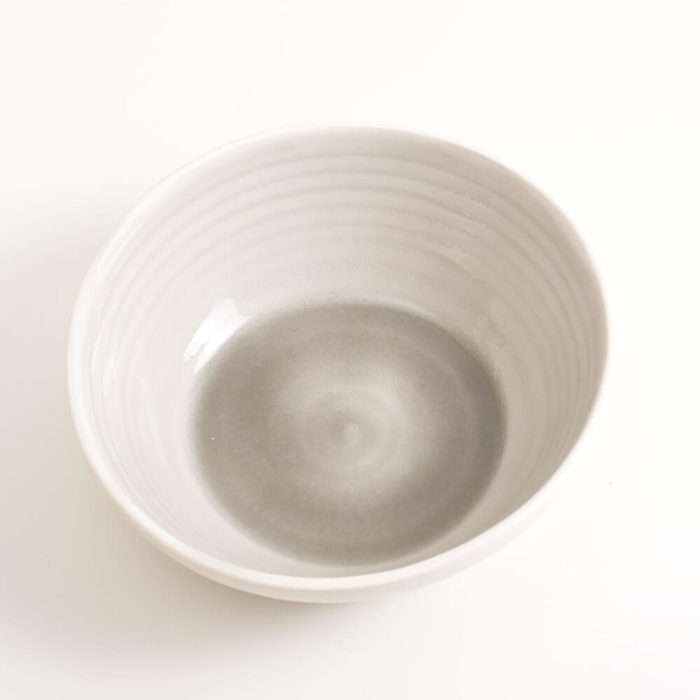 Handmade shallow porcelain bowl in grey. Hand-thrown with natural ridges and pale coloured pastel inside. Perfect for cereal or soup. Beautiful on its own or as part of a mix and match set. Available in 4 colours: Pink, blue, turquoise and grey.