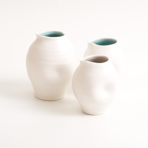 Handmade dimpled porcelain jug set. With a matt white glaze on the outside and soft coloured inside. Available in white, grey and turquoise, in two sizes. Perfectly formed dimples to fit in your hand. Handmade by Linda Bloomfield in London. Sold on chalkandmoss.com.