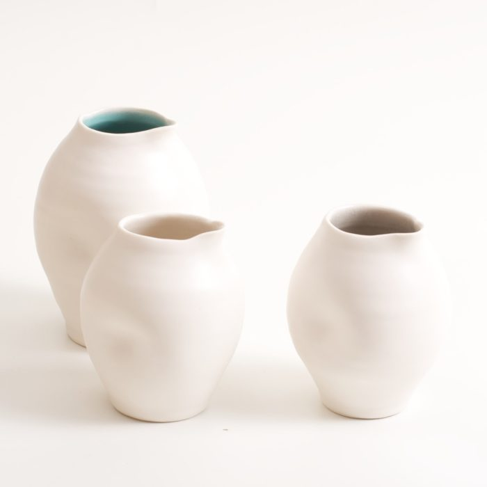 Handmade porcelain dimpled jug. With a matt white glaze on the outside and soft coloured inside. Available in white, grey and turquoise, in two sizes. Perfectly formed dimples to fit in your hand. Handmade by Linda Bloomfield in London. Sold on chalkandmoss.com.