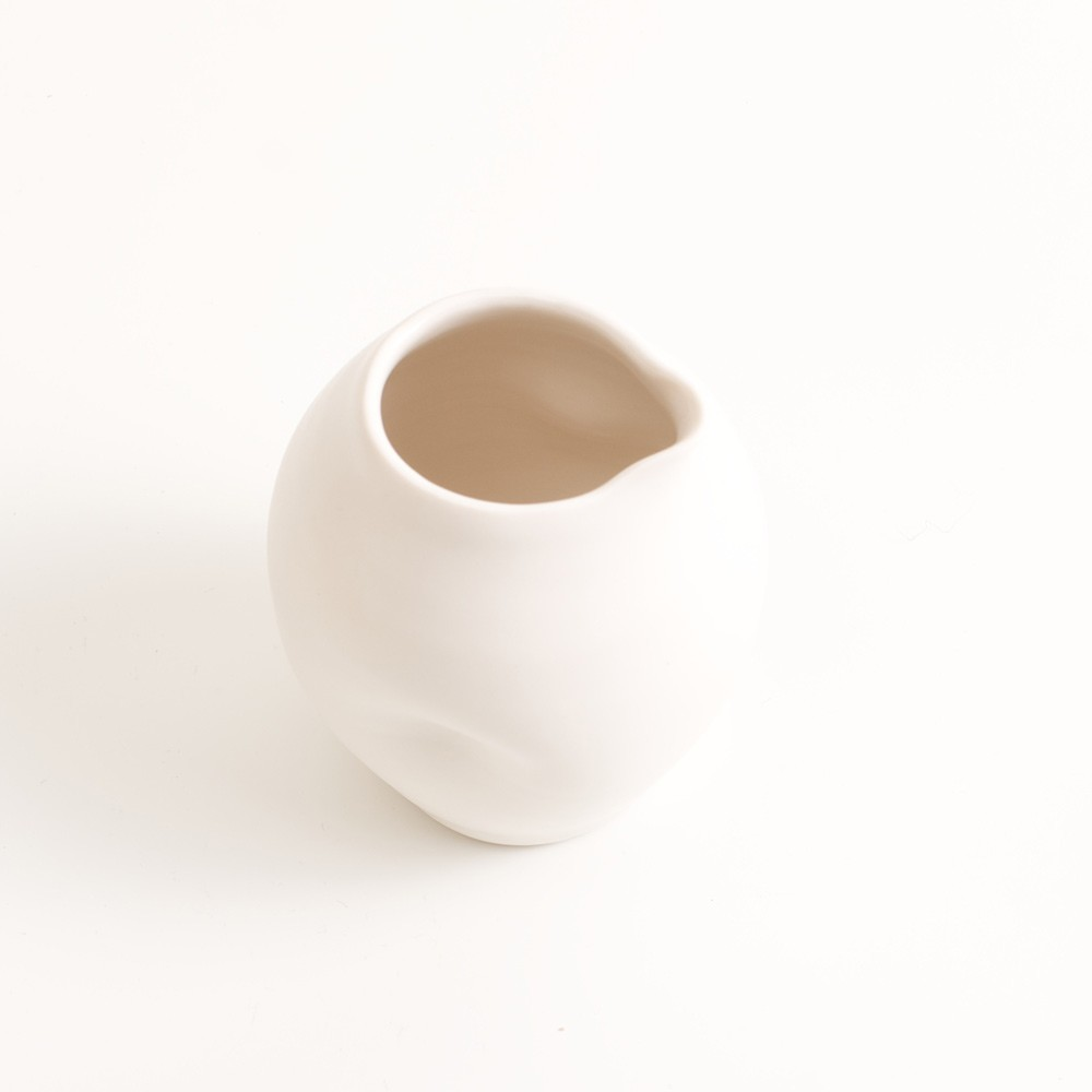 Handmade porcelain dimpled jug medium white. With a matt white glaze on the outside and soft coloured inside. Available in white, grey and turquoise, in two sizes. Perfectly formed dimples to fit in your hand. Handmade by Linda Bloomfield in London. Sold on chalkandmoss.com.
