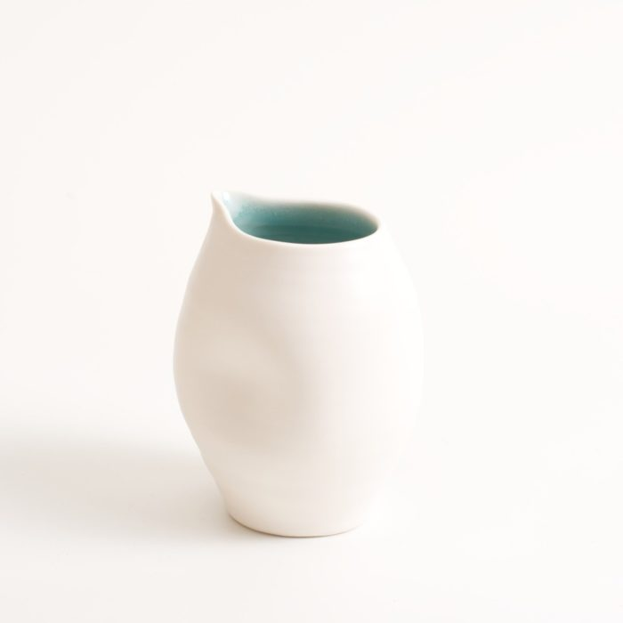 Handmade porcelain dimpled jug turquoise small. With a matt white glaze on the outside and soft coloured inside. Available in white, grey and turquoise, in two sizes. Perfectly formed dimples to fit in your hand. Handmade by Linda Bloomfield in London. Sold on chalkandmoss.com.