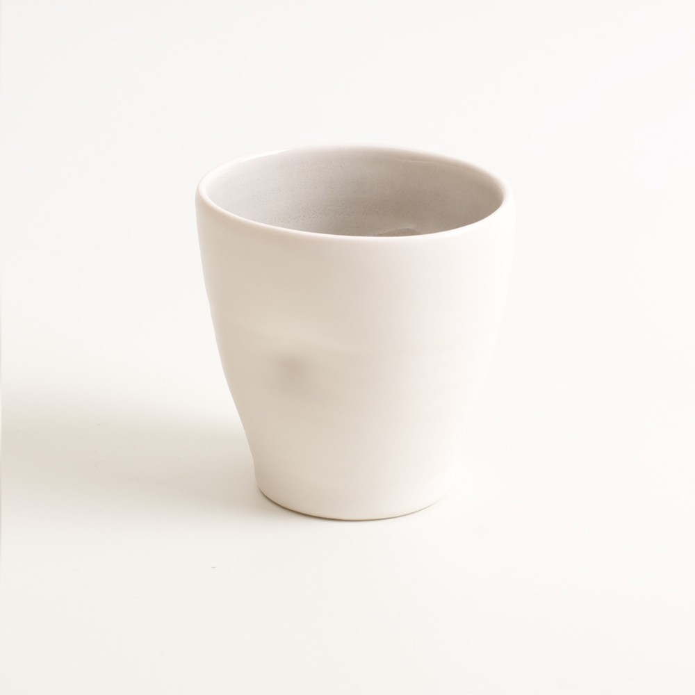 Handmade dimpled cup in grey. With a matt white glaze on the outside and soft coloured inside. Available in pale blue, pale pink, grey and turquoise. Perfectly formed dimples to fit in your hand, where the shape is inspired by Japanese tea traditions. Handmade by Linda Bloomfield in London. Sold on chalkandmoss.com.