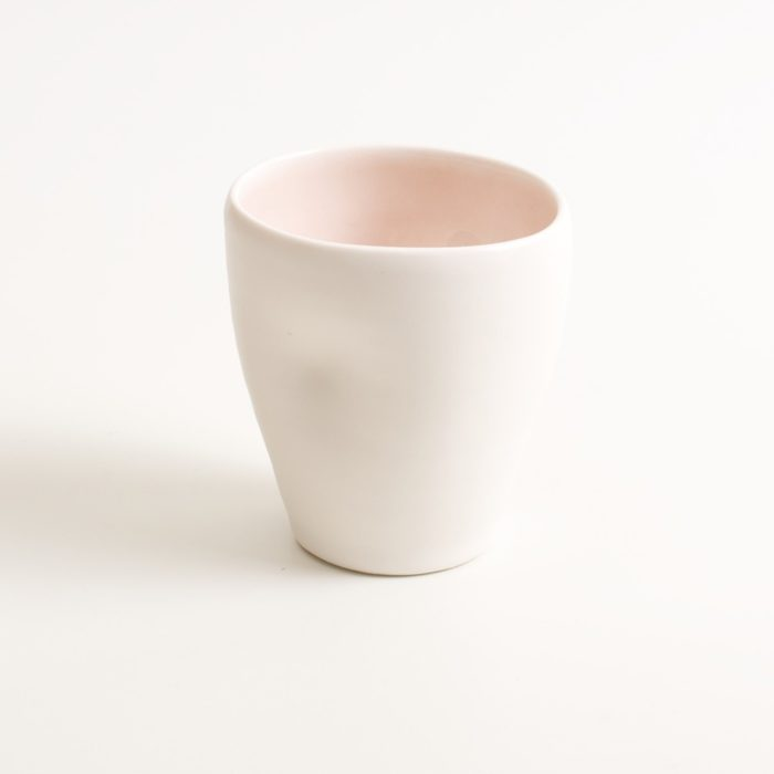 Handmade dimpled cup pink. With a matt white glaze on the outside and soft coloured inside. Available in pale blue, pale pink, grey and turquoise. Perfectly formed dimples to fit in your hand, where the shape is inspired by Japanese tea traditions. Handmade by Linda Bloomfield in London. Sold on chalkandmoss.com.