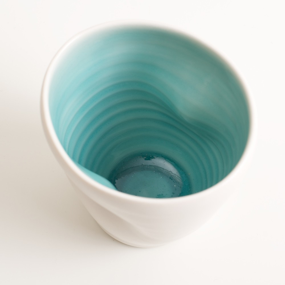 Handmade dimpled cup turquoise inside. With a matt white glaze on the outside and soft coloured inside. Available in pale blue, pale pink, grey and turquoise. Perfectly formed dimples to fit in your hand, where the shape is inspired by Japanese tea traditions. Handmade by Linda Bloomfield in London. Sold on chalkandmoss.com.