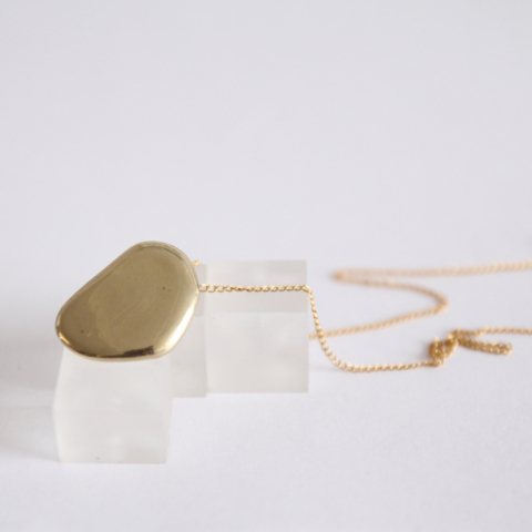 Gold Necklace 18 Carat - Dormant pendant from the Lava collection. This everyday pendant is a smooth, touchable drop of lava. Made from recycled brass and 18ct gold plate, on a gold filled chain.