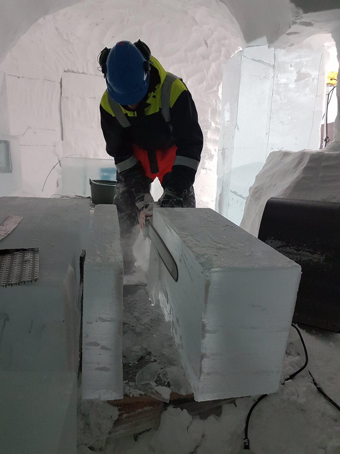 Building the ICEHOTEL involves sawing 200kg ice blocks that have come from the nearby river. They are cut up with chain saws and then cleaned up.