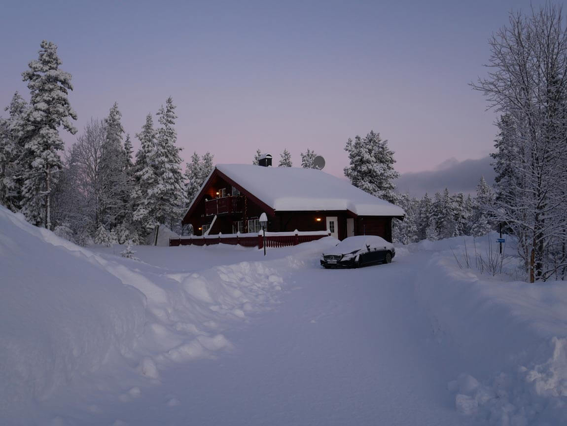 """I ett hus vid skogens slut"". A little cottage at the end of the woods, nestled among snowy pine trees."