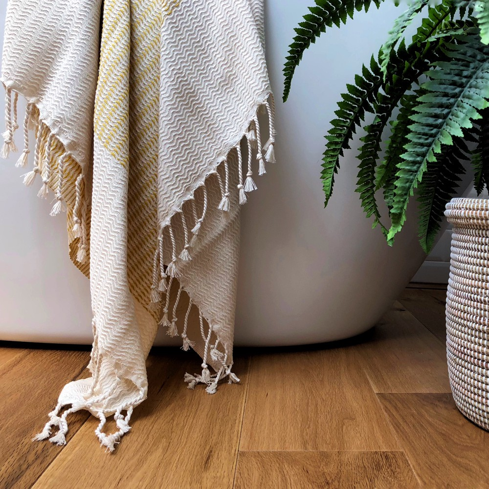 Lutti hammam towel - absorbent, compact and quick drying. 100% cotton and earth friendly dyes. Choose from mustard yellow, pebble grey, black or cobalt blue (seen here in mustard). Fish bone pattern, block ecru stripe, hand knotted fringing. 90 x 180 cm (bath sheet size).