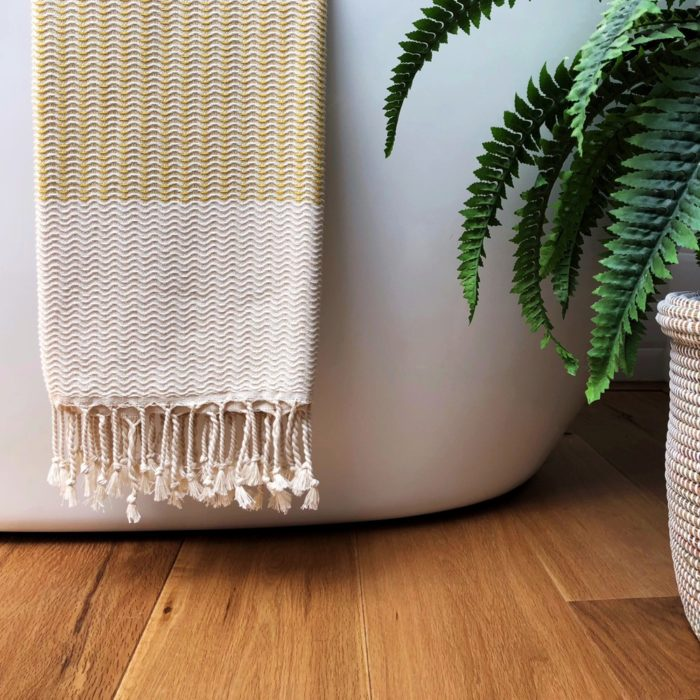 Hammam towel - Lutti - perfect draped over the bath, sofa or bed. Soft, absorbent, quick drying and compact. Available in yellow, grey, black or blue (seen here in mustard yellow). By Luks Linen, sold on Chalk & Moss.