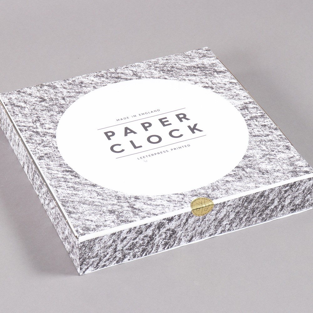 Paper clock, shown in its packaging. The clock is made from recycled paper with a sturdy back. By Wald, on Chalk & Moss (chalkandmoss.com).