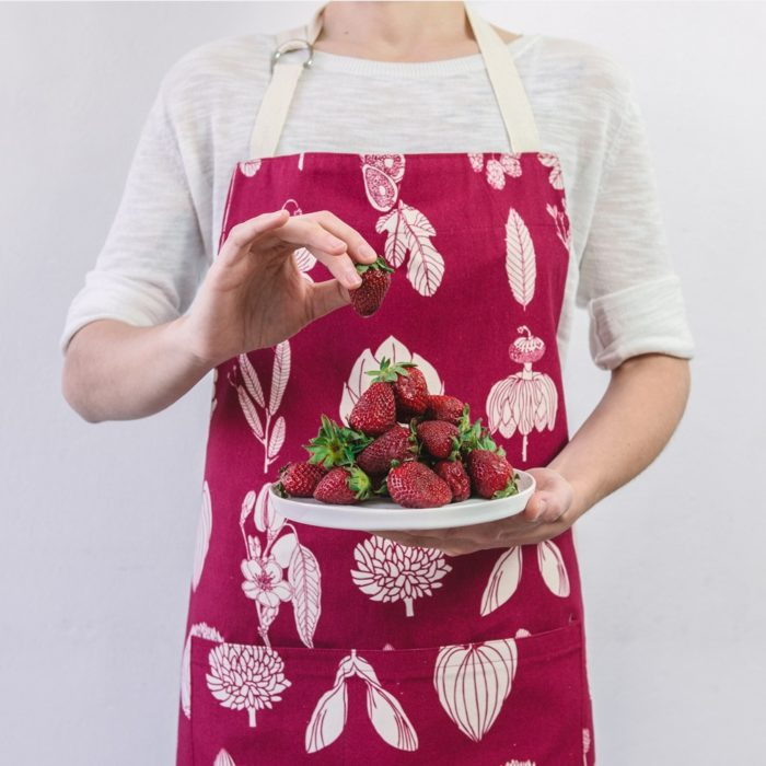 Botanical apron made from undyed cotton, and using water based dyes in the screen print. Available in several colours, seen here in raspberry red. By Softer + Wild, available on nature connected homeware shop Chalk & Moss.