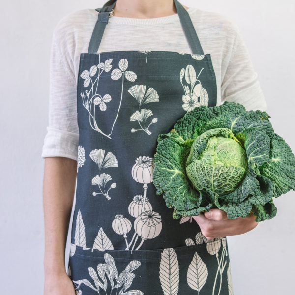 Botanical apron made from undyed cotton, and using water based dyes in the screen print. Available in several colours, seen here in charcoal. By Softer + Wild, available on nature connected homeware shop Chalk & Moss.