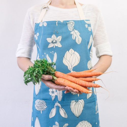 Botanical apron made from undyed cotton, and using water based dyes in the screen print. Available in several vibrant colours, seen here in kingfisher blue. By Softer + Wild, available on nature connected homeware shop Chalk & Moss.