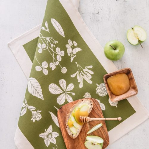 "Botanical tea towel in natural, un-dyed cotton by Softer + Wild. Hand screen printed in Sussex UK. Available in many vibrant colours, seen here in ""greenery""."