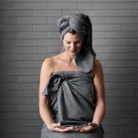 Extra large bath sheet ideal at the gym, yoga, spa, on the beach, or after a relaxing bath. Compact and quick drying, with a band to keep it in place and for hanging. Seen here in dark grey, more colours to choose from. 165 x 110 cm