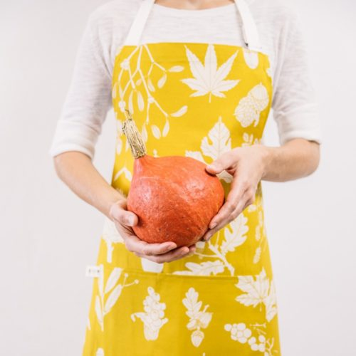 Mustard apron in botanical pine winter design. Designed and hand screen printed in Sussex, UK. Bring some Scandinavian happiness into your kitchen!