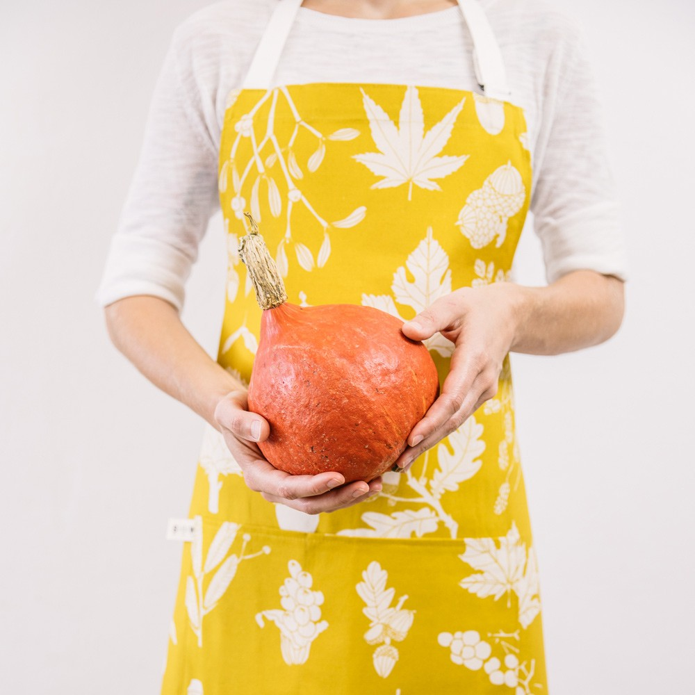 Screen printed apron in mustard yellow botanical pine winter design. Designed and hand screen printed in Sussex, UK. Bring some Scandinavian happiness into your kitchen!