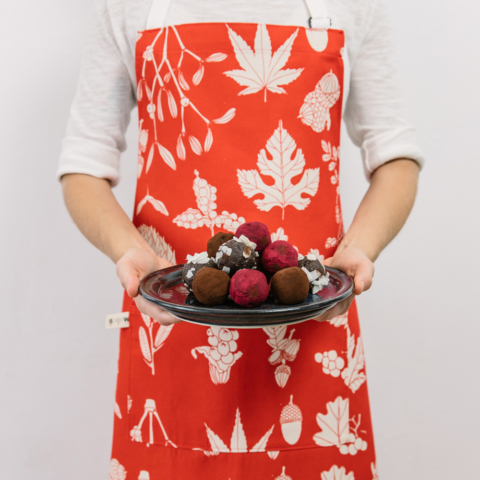 Screen printed apron in poppy red botanical pine winter design. Designed and made in Sussex, UK.