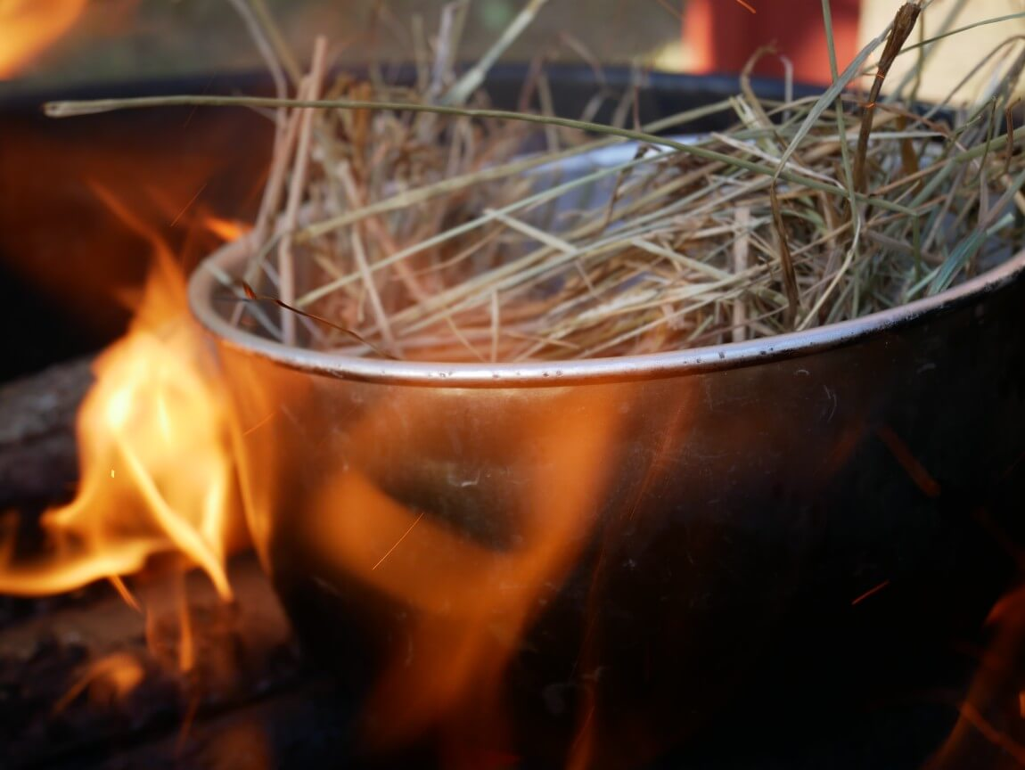 Char the hay / straw in a pan over the open fire (the pan will go black on the outside, so don't use grandma's best). It will catch fire and turn to char dust. Then mix with sea salt and grind, and use as seasoning.