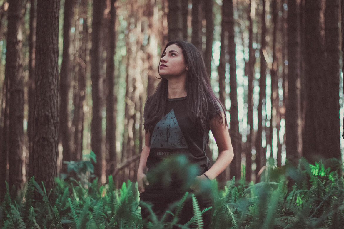 This woman is standing among the trees in the forest, looking up, contemplating, or perhaps looking at a bird. Spending time in nature does wonders for body and mind.