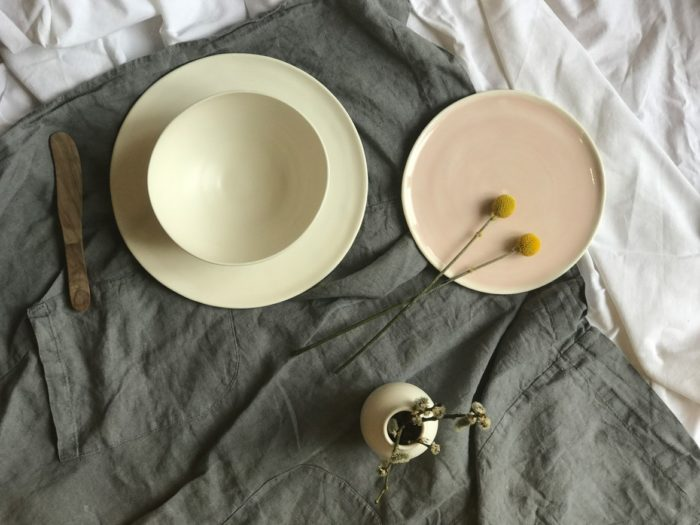 Linda Bloomfield's hand thrown porcelain dinnerware, including plates, bowls, jugs, mugs and vases. Collected here on a rustic, ruffled linen tablecloth.