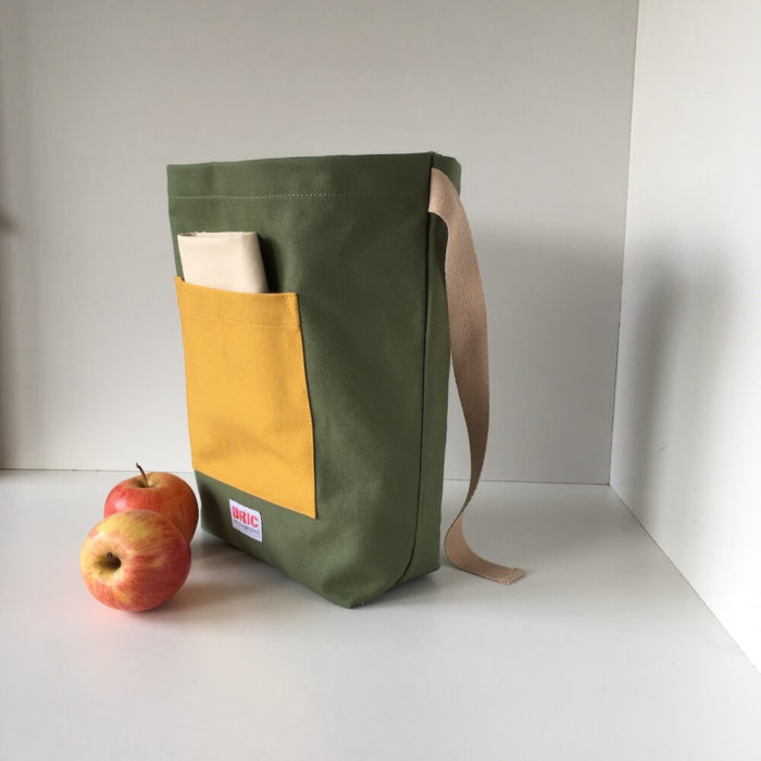 Eco friendly lunch bag - Furo Bric - with a furoshiki cotton lining, pocket and carry strap. Lunch bag available in fern green/gorse yellow and teal/gorse yellow.  Dimensions: H 25cm W 30cm Width at bottom 14cm, depth at bottom 9cm Optional extra lining.