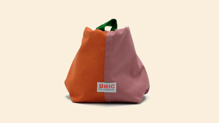 Bric Classic environmentally friendly cotton lunch bag with BPA free removable waterproof lining, perfect for cold food and hot leftovers. Rolls down to form a picnic bowl. Comes in several colours. Dimensions: H 25cm W 30cm Width at bottom 14cm, depth at bottom 9cm Optional spare washable lining. Seen here in orange and pink, tied.