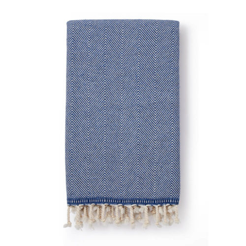 Wool throw made from an organic cotton and lambs wool blend, with a classic herringbone pattern. This makes it both warm and soft on the skin. 130 x 185cm. Seen here in denim (also available in grey).