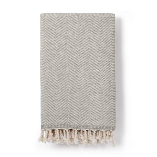 Wool throw made from an organic cotton and lambs wool blend, with a classic herringbone pattern. This makes it both warm and soft on the skin. 130 x 185cm. Seen here in grey (also available in denim blue).
